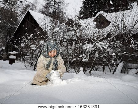 child plays in the snow. Winter. Girl in the village a shawl a sheepskin coat a lot of snow in mittens