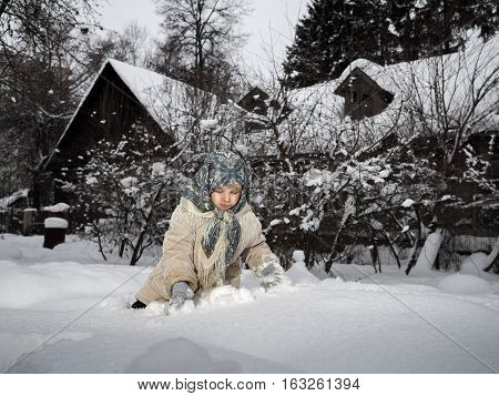 The little girl in the village playing in the snow
