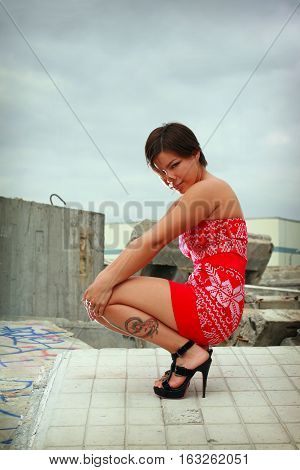 Young sexy girl in red gown and high shoes