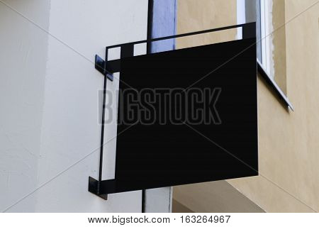 Mock up. Black square shape signboard on wall.