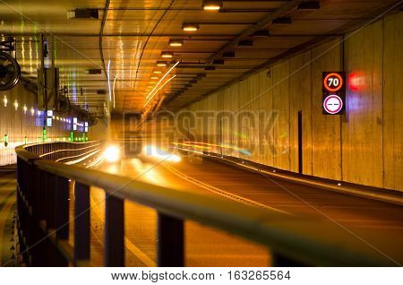 Truck driving through the tunnel by night. Tunnel with speed limit.