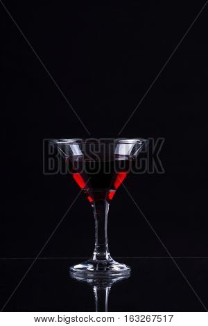 Red Wine In A Glass Of Martini On A Black Background