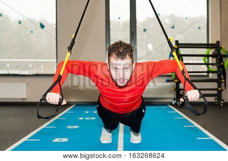 one white curly-haired, bearded sporty man exercising suspension push-up with fitness trx straps