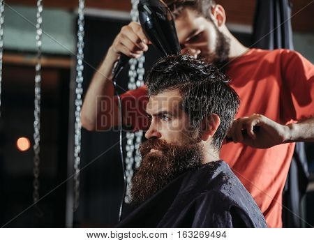 Handsome barber drying hair with drier makes hairstyle to bearded man with beard. Male customer sitting in chair in hairdressing saloon or barbershop