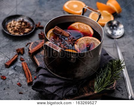 Mulled wine with orange, spices and strainer in aluminum vintage casserole on wooden board. Concrete background. Hot drink. Top view.