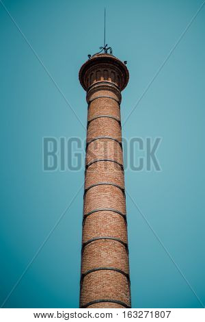View from bottom of brick chimney with arrester on top and regular metal ties on body clean teal sky behind Barcelona Spain