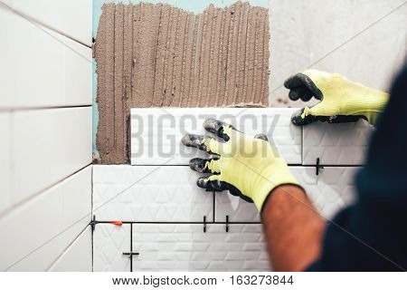 Industrial Construction Worker Installing Small Ceramic Tiles On Bathroom Walls And Applying Mortar