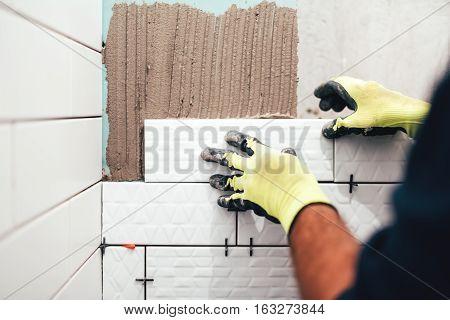 Industrial Construction Worker Installing Small Ceramic Tiles On Bathroom Walls And Applying Mortar