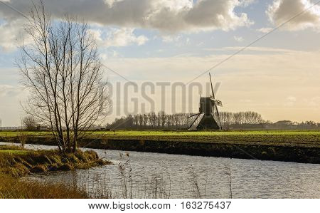 Picturesque backlit image of a polder landscape in the Netherlands on a cloudy day at the beginning of the winter season. In the background a hollow post mill with paddle wheel from 1699.
