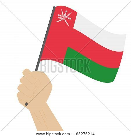 Hand holding and raising the national flag of Oman