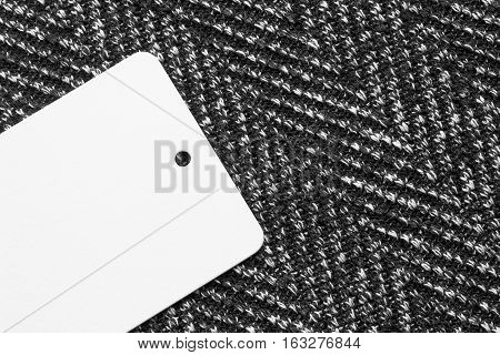 Blank white label on gray tweed as a background