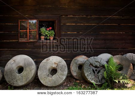Rustic window with colourful flower pots of geraniums and round grindstones