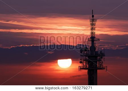 Steel tower with antennas with the beautiful red sunset as a background. Cracow, Poland. Antenna tower silhouette