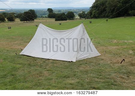 A Small White Tent Pitched on a Sloping Meadow.