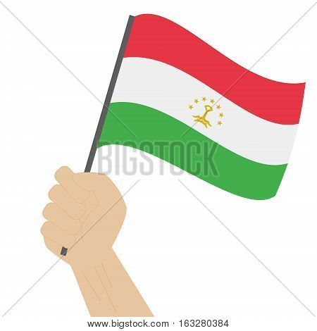 Hand holding and raising the national flag of Tajikistan