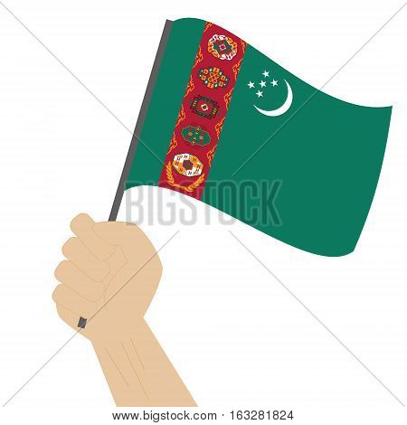 Hand holding and raising the national flag of Turkmenistan