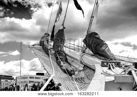 Details of bowsprit and gathered sail of the tall ship on the cloudy sky background.