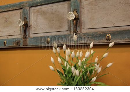 Silk and paper flower bouquet used for home décor, set against yellow wall of room and old wood door hanging as interesting backdrop.