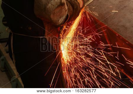 Welder used grinding stone on steel in factory with sparks