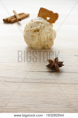 One scoop of homemade Gingerbread Ice Cream on brown wooden background surrounded by cinnamon sticks and star anise. Focus on scoop of ice cream and copy space in the front.