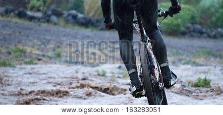 Mountain bikers driving in rain upstream creek