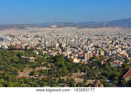 View of ancient temple of Hephaestus in Agora and city of Athens in Greece