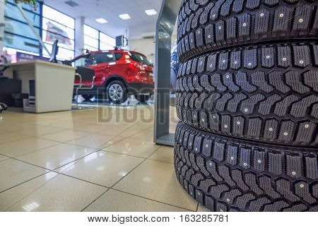 Studded new winter tires in showroom of a car dealer