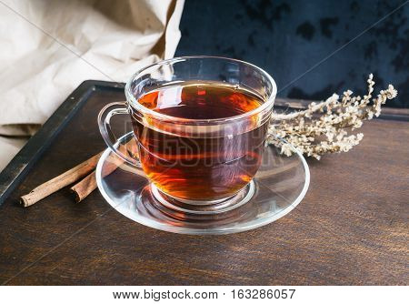 Sagebrush twig cup of tea and cinnamon sticks on dark wooden background