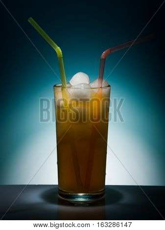 Tall glass with a drink and ice on blue background