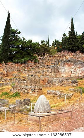 The view on Omphalos or Baetylus, the famous religious stone artifact, that was the center of the Universe for ancient greeks, Delphi, Greece