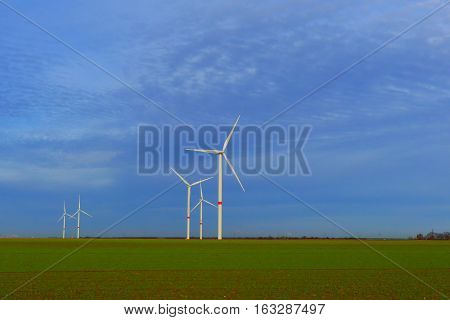This is a wind turbine farm in Oberwichterich. Oberwichterich is a small town in Germany. It is winter and a shinny day.