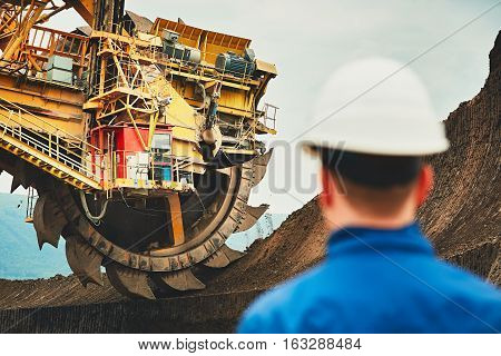 Coal mining in an open pit. Miner looking on the huge excavator. Industry in the Czech Republic Europe