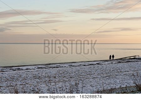 Couple walking at the beach at sunset