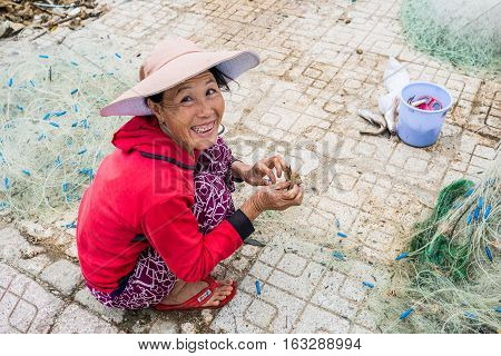 Nha Trang VIETNAM - December 282016 : Vietnamese woman fisherman unravels fishing net