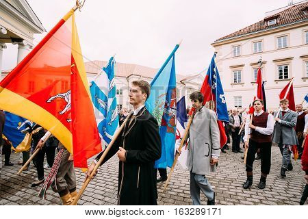 Vilnius, Lithuania - July 6, 2016: Young men dressed in traditional costumes take part in ceremonial procession with flags on Statehood Day. Holiday in commemorate coronation in 1253 of Mindaugas King.