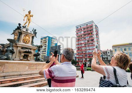Batumi, Adjara, Georgia - May 26, 2016: Tourists photographed of the Neptune Fountain in park on Rustaveli Ave. Famous landmark.
