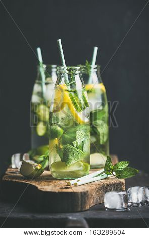 Citrus fruit and herbs infused sassi water for detox, healthy eating or dieting in glass bottles with straws, dark background, selective focus. Clean eating, weight loss or healthy lifestyle concept