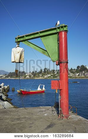 CONCON, CHILE - NOVEMBER 28, 2016: Hoist for lifting fishing boats out of the water on a jetty at Concon on Pacific Coast of Chile.