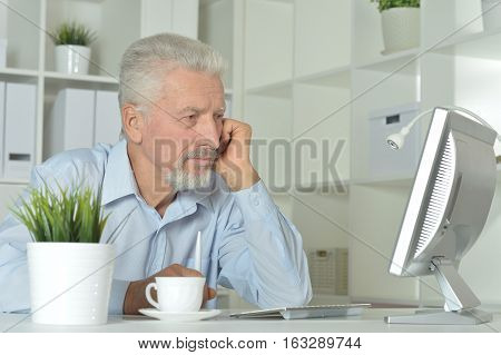 Portrait of a senior man using computer at office