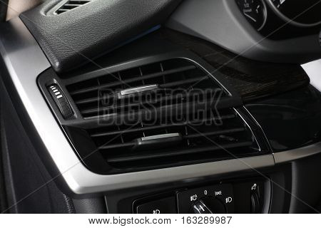 Interior of leather passenger compartment of the car in dark tones. Climate control