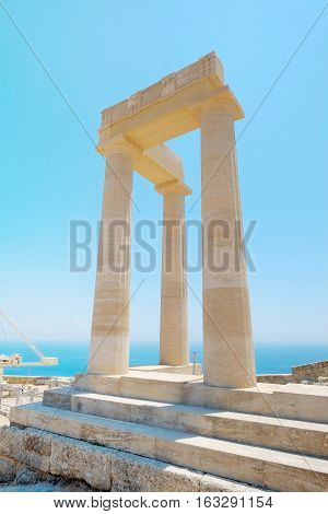 Famous Greek temple pillar against clear blue sky and sea in Lindos Acropolis Rhodes Athena Temple Greece
