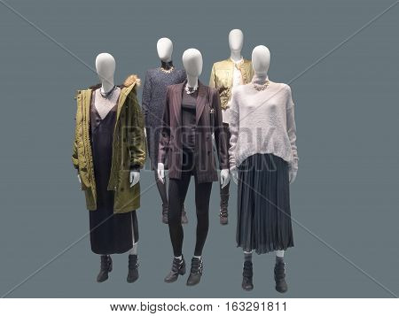 Group of female mannequins wear fashionable autumn winter clothes isolated. No brand names or copyright objects.