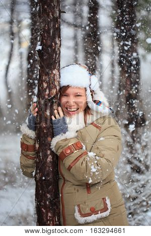Smiling Woman In Coat With White Fur, Hat With Ear Flaps And Grey Fingerless Knitted Mittens Hugs A