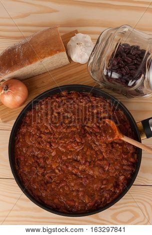 Chili Con Carne in pan on wooden table, above pan onion, garlic, bread, and beans