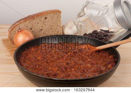 Chili Con Carne in pan on wooden table, on background onion, garlic, bread and beans