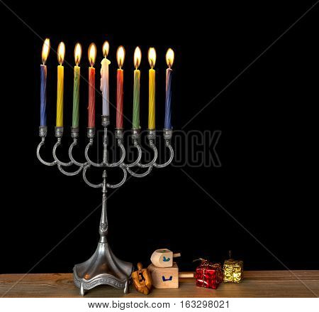 Menorah with the glitter lights of candles and wooden dreidels are traditional Jewish symbols for Hanukkah holiday. Low key image with a black background for inspiration of retro style and feast ceremony