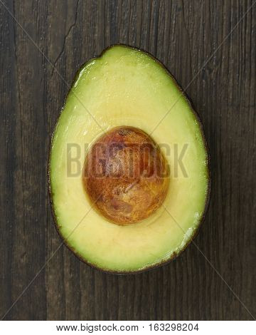 A single sliced avocado half on a wood surface