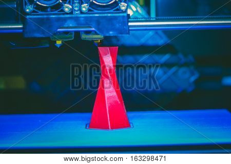3D printer printing isolated volume triangular object red color on the basis of blue and black background close-up. Modern 3d printing technology