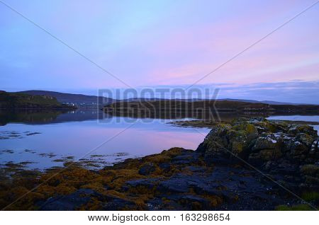 Calm waters of Dunvegan loch with pastel skies.