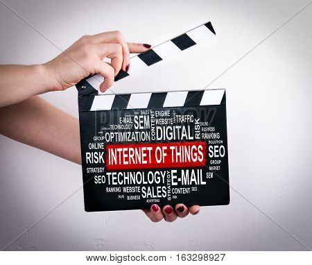 Internet of things concept. Female hands holding movie clapper.